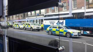 Police surrounding the coach on High West Street