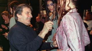 In this file photo taken on January 18, 1999 French designer Emanuel Ungaro checks a dress on a model before his 1999 Spring/Summer Haute Couture collection in Paris