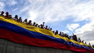 Bandera de Venezuela con personas sobre ella.
