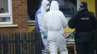 Police and forensic officers outside a house in Broom Close, Twinbrook