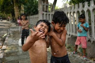 Children cool themselves off along a highway as they bathe on a hot afternoon, near Nizamuddin, on June 2, 2019 in New Delhi, India