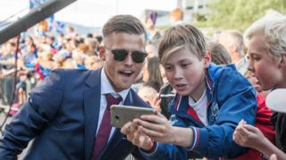 Iceland's midfielder Arnor Ingvi Traustason poses for photograph as he arrives with his team in Reykjavik on July 4, 2016 while people in the street