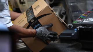 Worker assembles a box for delivery at the Amazon fulfilment centre.