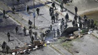 Miembros de la policía venezolana se refugian detrás de una barricada en Caracas.