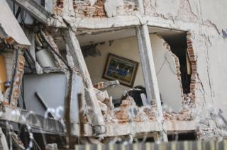 A damaged building with a hole in the exterior reveals a painting hanging on the wall inside - showing a tranquil boating scene