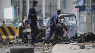 Somali security force personnel walk near the wreckage of a burnt-out vehicles at the site of a car bomb explosion near the building of the Interior Ministry in Mogadishu on July 7, 2018