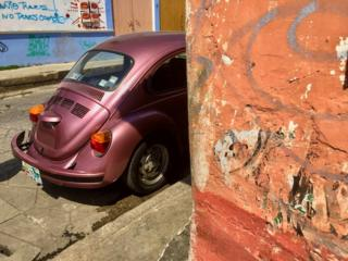 Volkswagen Beetle sticking out from behind the corner of a wall