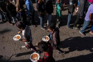 A group of Central American migrants are seen lining up for food outside a temporary shelter at the US-Mexico border in Tijuana, Baja California state, Mexico, on 23 November