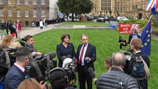 Arlene Foster and Nigel Dodds talk to reporters outside the House of Commons