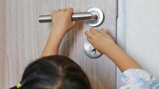 طفلة تحاول فتح باب