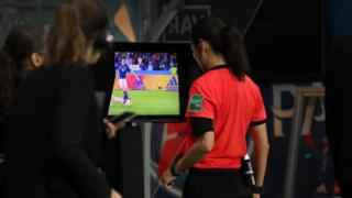 A referee looking at the VAR monitor.