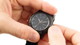 Homem mexe em relógio