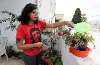 A woman wearing a T-shirt bearing Che Guevara's face waters potted plants on a balcony.