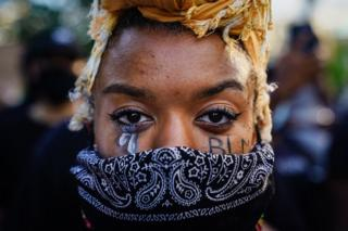 """A woman with """"BLM"""" written on her cheek poses during a demonstration"""