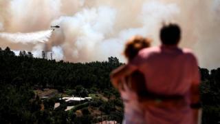 Португалия, август 2018 г.: пожарные заливают горящий лес водой с вертолета