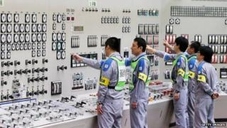 Operators check monitors of the nuclear reactor in the central control room of the Kyushu Electric Power Sendai nuclear power plant on August 14, 2015.