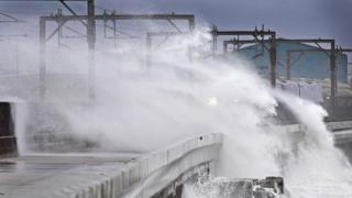 Train passes through waves at Saltcoats in North Ayrshire