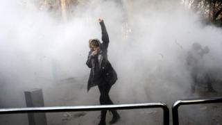 An Iranian woman raises her fist during a protest in Tehran on 30 December 2017