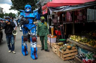 healthy fod for babies A man wearing a Transformers costume walks past a food stall