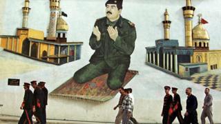 Фреска: Саддам Хуссейн на молтвенном коврике