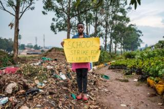 Leah Namugerwa, a 15-year-old climate activist, holds a placard in the Ugandan city of Kampala