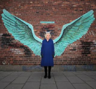 The Duchess of Cornwall stands between the wings of artist Paul Curtis's mural entitled For All Liverpool's Liver Birds, in Liverpool's Baltic Triangle