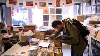 A customer browses through the racks at the music shop Record Collector in Sheffield