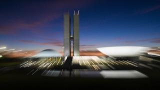 Foto desfocada mostra prédio do Congresso em Brasília no anoitecer