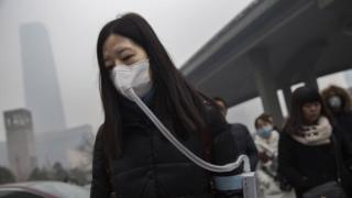 A woman wears a mask and filter as she walks during heavy pollution in Beijing, China