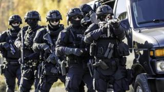 Policiais da SWAT segurando armas