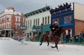 Rider Jeff Dahl races down Harrison Avenue towing skier and son Jason Dahl