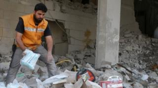 A Red Crescent aid worker inspects scattered medical supplies after an air strike on a medical depot in the rebel-held Tariq al-Bab neighbourhood of Aleppo (30 April 2016)