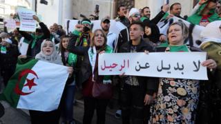 """Waandamanaji wa Waalgeria wakiwa wamebeba mabango yaliyoandikwa maandishi ya kiarabu """"hakuna mbadala zaidi ya kuondoka"""" wakati wa maandamano dhidi ya kuongezwa kwa muda wa urais kwa Abdelaziz Bouteflika mjini Algiers, Algeria"""