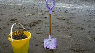 A bucket and spade on a grey summer day on the beach at Sandsend, near Whitby, North Yorkshire.
