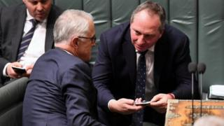 Australian PM Malcolm Turnbull (L) speaks to his deputy, Barnaby Joyce, in parliament