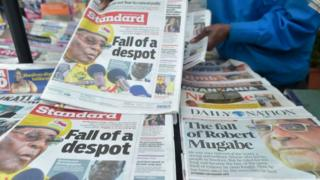 A newspaper vendor arranges local dailies with headlines about the situation in Zimbabwe on November in Nairobi
