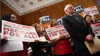 Bernie Sanders stands with supporters of Medicare for All holding signs