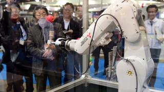 A Mitsubishi Electric robot plays a cup and ball game