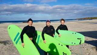 Three women with surfboards