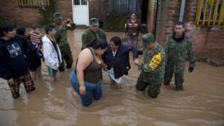 Rescuers help women near a flooded house in Mexico