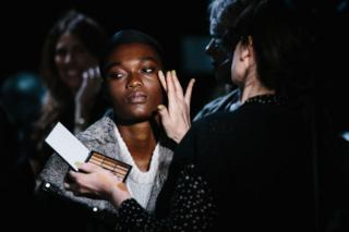 A model gets her make up done at the backstage before the Michael Kors Fashion