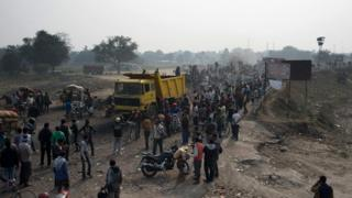 Bystanders look on as cargo trucks pass through the India-Nepal border at Birgunj on Friday