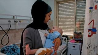 شابة فلسطينية تتطوع كأم بديلة لرضيع من غزة يعالج وحيدا في الخليل