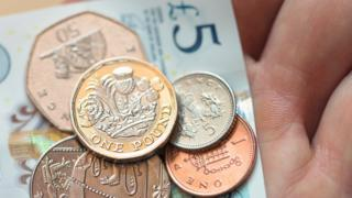 A selection of coins lie on top of a five pound note held in someone's hand