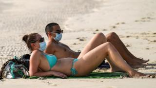A man and woman lying on a beach wearing face masks