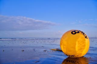 A buoy on a beach at sunrise