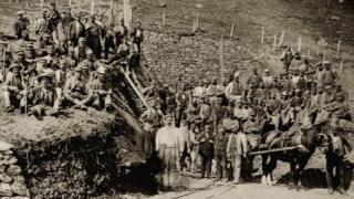 About 50 workers pose for an official photograph with a horse and cart also in view