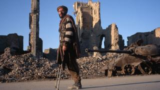 A man who lost his leg to a land mine walks past bomb-destroyed buildings