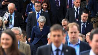 Theresa May leaves the conference centre in Manchester