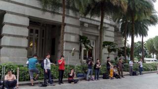 Reporters outside Kim's hotel